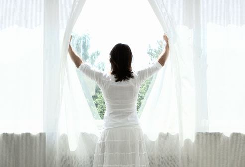 getty_rm_photo_of_woman_opening_curtains